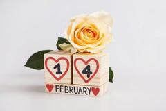 Valentine's-Tageszusammensetzung mit hölzerner Kalender- und Gelbrose Lizenzfreie Stockfotos