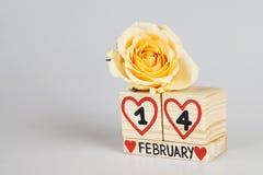 Valentine's-Tageszusammensetzung mit hölzerner Kalender- und Gelbrose Stockbilder