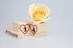 Valentine's-Tageszusammensetzung mit hölzerner Kalender- und Gelbrose Lizenzfreies Stockfoto