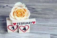 Valentine's-Tageszusammensetzung mit hölzerner Kalender- und Gelbrose Lizenzfreie Stockbilder