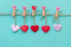 Valentineâs Tag Genähte Kissenherzen rudern Grenze auf den roten, rosa und weißen Wäscheklammern an der rustikalen blauen Pastell stockbild