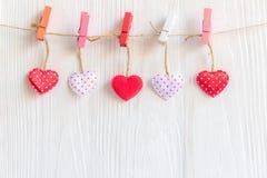 Valentineâs Tag Genähte Kissenherzen rudern Grenze auf den roten, rosa und weißen Wäscheklammern an den rustikalen weißen hölzern lizenzfreies stockbild