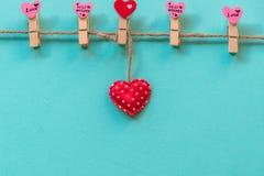 Valentineâs Tag Genähte Kissenherzen rudern Grenze auf roten Wäscheklammern an den rustikalen weißen hölzernen Planken stockfoto