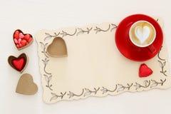 Valentine& x27 υπόβαθρο ημέρας του s κόκκινο φλιτζάνι του καφέ με τον αφρό και τη σοκολάτα μορφής καρδιών Τοπ εικόνα άποψης Στοκ Φωτογραφίες