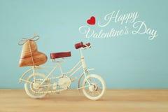 Valentine& x27; 与白色葡萄酒自行车玩具的s天浪漫对此的背景和心脏在木桌 免版税库存照片
