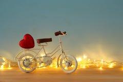 Valentine& x27; 与白色葡萄酒自行车玩具的s天浪漫对此的背景和心脏在木桌 库存图片