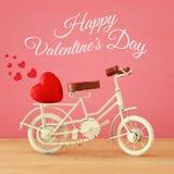 Valentine& x27; 与白色葡萄酒自行车玩具的s天浪漫对此的背景和心脏在木桌 库存照片