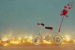 Valentine& x27; 与白色葡萄酒自行车玩具的s天浪漫背景和对此的闪烁红色心脏在木桌 免版税库存图片