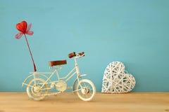 Valentine& x27; 与白色葡萄酒自行车玩具的s天浪漫背景和对此的闪烁红色心脏在木桌 免版税图库摄影