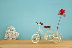 Valentine& x27; 与白色葡萄酒自行车玩具的s天浪漫背景和对此的闪烁红色心脏在木桌 库存图片