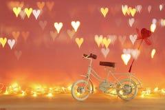 Valentine& x27; 与白色葡萄酒自行车玩具的s天浪漫背景和对此的闪烁红色心脏在木桌 免版税库存照片