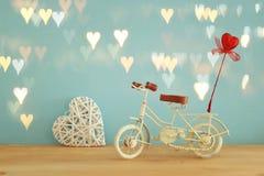 Valentine& x27; 与白色葡萄酒自行车玩具的s天浪漫背景和对此的闪烁红色心脏在木桌 库存照片