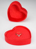 Valentine. Heart-shaped valentines day box with lid off and diamond ring inside on white background Stock Photography