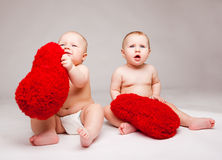 Valentine babies with  fluffy hearts. Cute valentine babies with red fluffy hearts, over gray Stock Photos