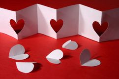 Valentine background. White folded paper with heart holes placed over red paper Stock Image