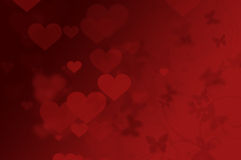 Valentine background. Red love background - defocused hearts, butterflies and swirls. Butterflies in the stomach Royalty Free Stock Photo