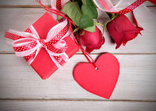 Valentine background of gift box, red roses and red gift tag Stock Images