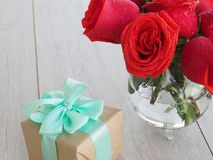 Valentine background of gift box with ribbon and bow and bunch of red roses on wood. Space for copy. Stock Photography