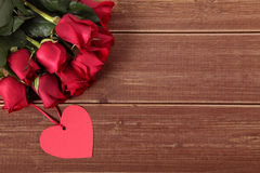 Valentine background of heart shape gift tag and red roses on wood. Space fo Royalty Free Stock Images