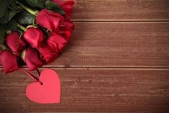 Valentine background of heart shape gift tag and red roses on wood. Space fo Stock Images