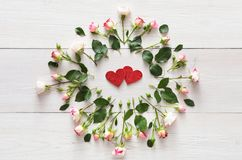 Handmade glitter hearts in pink natural roses frame on white rustic wood stock images