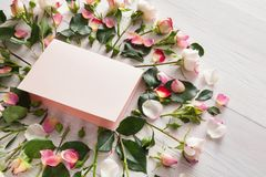 Handmade paper card in pink natural roses frame on white rustic wood stock images