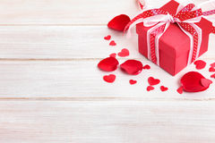 Valentine background of red gift box and rose petals on white wood. Royalty Free Stock Photos