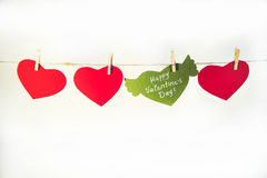 Valentine background with sewed pillow hearts row border on red clothespins at rustic white wood planks. Happy lovers. Day card mockup, copy space Royalty Free Stock Photo