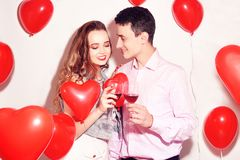 Valentine Beauty couple with red air balloons heart drinking red wine. Beautiful Happy Young woman and man hugs. Joyful lover stock photography
