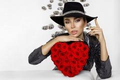 Valentine Beauty flicka med röda hjärtarosor Stående av en ung kvinnlig modell med gåvan och hatten som isoleras på bakgrund royaltyfri bild