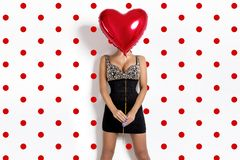 Valentine Beauty girl with red air balloon portrait, isolated on polka dots background. Model covers her face with a balloon. royalty free stock photography