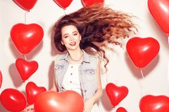 Valentine Beauty girl with red air balloons laughing, on white background. Beautiful Happy Young woman. Womans day. Holiday party. stock image