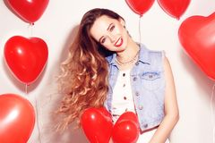 Valentine Beauty girl with red air balloons laughing, on white background. Beautiful Happy Young woman. Womans day. Holiday party. stock images
