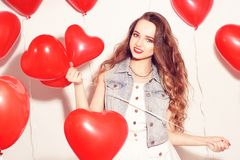 Valentine Beauty girl with red air balloons laughing, on white background. Beautiful Happy Young woman. Womans day. Holiday party. royalty free stock photo
