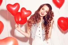Valentine Beauty girl with red air balloons laughing, on white background. Beautiful Happy Young woman. Womans day. Holiday party. royalty free stock image