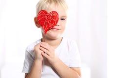 Valentine boy. Little caucasian boy shows a red Valentine heart Royalty Free Stock Photos