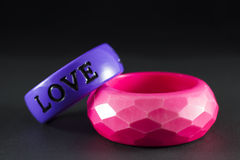 Valentine bracelets. Purple love engraved valentine bracelet and pink stylistic collet Royalty Free Stock Image