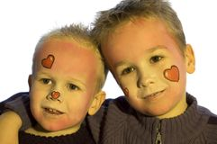 Valentine Brothers. Two lovely brothers with painted heart faces. Use it for valentine designs or just as a love picture royalty free stock photo