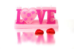 Valentine candle with sweets. Valentine candle shaped as word Love with sweets royalty free stock image