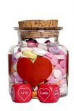 Valentine candy. A bottle of valentine candy hearts with loving message on some dice Royalty Free Stock Photography