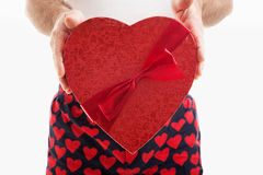 Valentine Candy Heart Gift. Man in hear underwear holding a big red Valentines Day heart filled with chocolate candy. White background stock photography