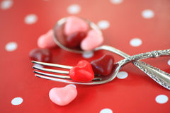 Valentine candy hearts on fork and spoon Stock Photography