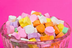 Candy Hearts. Valentine candy hearts piled high in a glass bowl with a pink textured background Stock Photography
