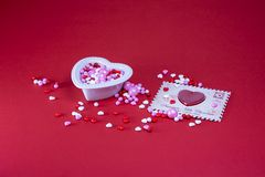 Valentine candy on a red background. Small heart shaped bowl filled with red white pink round and heart shaped coated candy next to an envelope with heart shaped royalty free stock photo