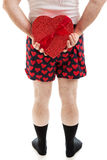 Valentine Candy Surprise. Man in heart underwear holding a box of Valentine's Day candy behind his back. Isolated on white royalty free stock image
