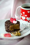 Valentine cappuccino cake and coffee. A small, delicious cappuccino cake , coated with chocolate chips, and decorated with a pink and red heart made from Stock Image