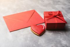 Valentine card with red envelope, gift box and heart gingerbread on grey textured background. Valentine card with red envelope, gift box and heart gingerbread Stock Photos