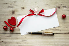 Valentine card with red heart and pen over wooden background Stock Images