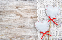 Valentine card with textile hearts on lacy cloth and old wood Royalty Free Stock Image