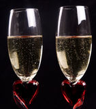 Valentine Celebration. Two glasses filled with champagne with a heart design for valentines celebration Royalty Free Stock Images